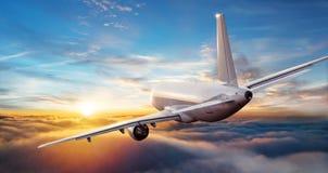 Kommersiell flygplanjetflygplan som flyger ovannämnda moln i härlig su Arkivfoto