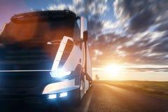 Kommersiell lastleveranslastbil med släpet som kör på huvudvägen på solnedgången Arkivfoto