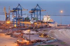 Kommersiell port för hav på natten i Mariupol, Ukraina Industriellt beskåda Lastfraktskepp med den arbetande kranbron i havsport Arkivfoto