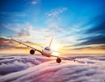 Kommersiellt flygplan för passagerare som flyger ovannämnda moln Royaltyfria Bilder
