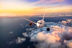 Kommersiellt flygplan för passagerare som flyger ovannämnda moln Arkivbild