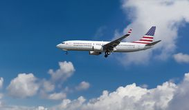 Kommersiellt flygplan med amerikanska flaggan på svans- och flygkropplandningen, blå bakgrund för molnig himmel royaltyfria bilder