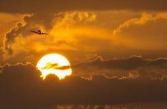 Kommersiellt flygplan på inställning ovanför stor sommarsoluppgång Arkivfoton