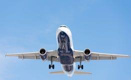 Kommersiellt flygplanflyg i blå himmel, full klaff och landningge royaltyfri foto