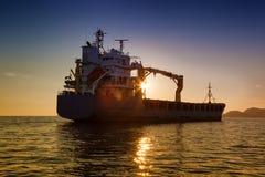 Kommersiellt lastfartyg på solnedgången Royaltyfri Foto