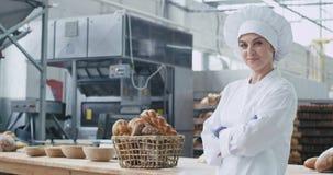 Kommersiellt stort leende för attraktiv kvinnabagare i en bageribransch som ser rak av bära för kameracloseup lager videofilmer