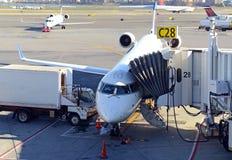 Kommersiellt strålflygplan på grov asfaltbeläggning som laddar dess last på flygplatsen Arkivbild