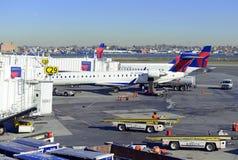 Kommersiellt strålflygplan på grov asfaltbeläggning som laddar dess last på flygplatsen för flyg Arkivbilder