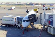 Kommersiellt strålflygplan på grov asfaltbeläggning som laddar dess last på flygplatsen för flyg Royaltyfri Bild