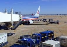 Kommersiellt strålflygplan på grov asfaltbeläggning som laddar dess last på flygplatsen för flyg Arkivbild