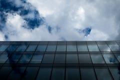 Kommerzielles modernes Glasbürogebäude gegen bewölkten Himmel in der Perspektive stockbild