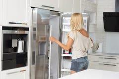 Kommerzielles nettes Mädchen vor Kühlschrank Stockbild