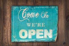 Kommet in är vi det öppna tecknet på en gammal träbakgrund Arkivfoton