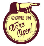 Kommna in, är vi öppna! Dörren shoppar det välkomnande tecknet med att peka fingret Royaltyfri Bild