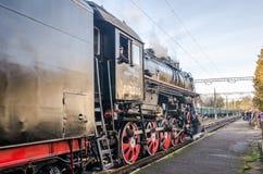 Kommt sowjetische Dampflokomotive der alten Weinlese des Eisenschwarzen Retro- mit rotem Stern zu dem Bahnhof, um Passagiere im c Lizenzfreie Stockfotografie