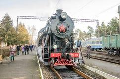 Kommt sowjetische Dampflokomotive der alten Weinlese des Eisenschwarzen Retro- mit rotem Stern zu dem Bahnhof, um Passagiere im c Stockbild