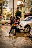 Kommunal arbetare i den regniga gatan Arkivfoto