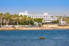 Kommunal sandstrand och Almyra hotell i Paphos, Cypern Presentera medelhavs- arkitektur, royaltyfri bild