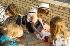 Kommunikations- und Erholungsgruppe von 4 Kinderjugendlichen Freunde spielen das Brettspiel und werfen Würfel Hintergrundstadtstr lizenzfreie stockfotos