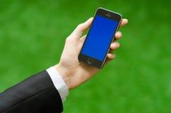 Kommunikations-und Geschäfts-Thema: Übergeben Sie in einem schwarzen Anzug, der ein modernes Telefon mit blauem Schirm im Hinterg Lizenzfreie Stockfotos