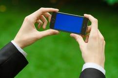 Kommunikations-und Geschäfts-Thema: Übergeben Sie in einem schwarzen Anzug, der ein modernes Telefon mit blauem Schirm im Hinterg Stockfotografie