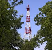 Kommunikationsmast på en bakgrund av blå himmel och gröna träd fotografering för bildbyråer