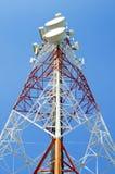 Kommunikationstorn med antenner mot blå himmel Arkivbild