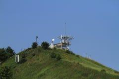 Kommunikationstorn som är höga på en kulle Arkivbild