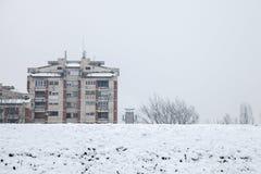 Kommunistiska husbyggnader framme av en djupfryst kulle i Pancevo, Serbien, under en eftermiddag med snö Arkivfoton
