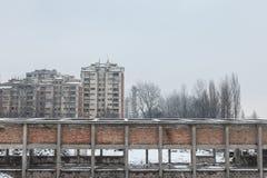 Kommunistiska husbyggnader framme av ett övergett lager i Pancevo, Serbien, under en kall eftermiddag under snön Royaltyfri Bild