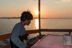 Komodo Sunset Guitar Player. Komodo island sunset boat tour Stock Photos