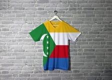 Komoren-Flagge auf Hemd und Hängen an der Wand mit Ziegelsteinmustertapete lizenzfreie stockfotografie