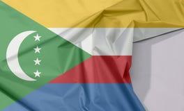 Komoren-Gewebeflaggenkrepp und -falte mit Leerraum lizenzfreie stockfotografie