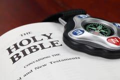 Kompaß auf geöffneter Bibel Stockfotografie