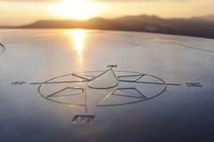 Kompaßzeichen am Sonnenuntergang Lizenzfreie Stockbilder