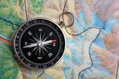 Kompaß auf Geographiekarte Stockfotos