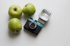 Kompakt filmkamera och tre gröna äpplen royaltyfria bilder