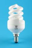 Kompakt fluorescerande energi - sparande ljus kula som isoleras på den blåa bakgrunden arkivfoton