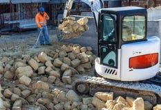 Kompakt inert material för grävskopa med hjälpen av en arbetare Royaltyfri Foto