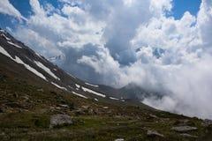 Kompakta vita moln i den blåa himlen är det högt i berg Royaltyfri Bild