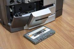 Kompakte Kassette und Magnetband- für Tonaufzeichnungenspieler auf Tabellenholzhintergrund lizenzfreie stockfotos