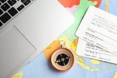Kompas, bilety i laptop na światowej mapie, mieszkanie nieatutowy obrazy royalty free