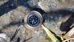 Kompas die op een rots dichtbij het water liggen en gericht op het Westen stock videobeelden