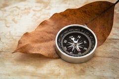 Kompas en droog blad op oude houten achtergrond, uitstekende stijl Stock Fotografie