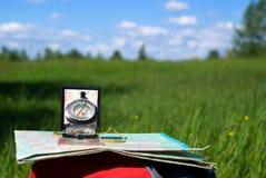 Kompas en kaart op rugzak Stock Foto's