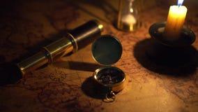 Kompas en kijker op oude wereldkaart in kaarslicht stock footage
