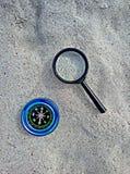 Kompas en meer magnifier op zand stock foto's
