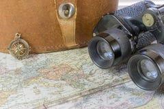 Kompas en uitstekende verrekijkers die op oude wereldkaart zitten stock foto's