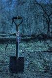 Kompas het hangen op een sapper schop op een vage achtergrond van geheimzinnige bomen bij nacht Royalty-vrije Stock Fotografie