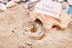 Kompas in het zand met Bericht - het Leven is een avontuur Royalty-vrije Stock Afbeeldingen